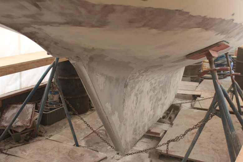 And one last shot of the bottom, again showing the aperture filled and rudder channel built into the trailing edge of the keel.  The waterline had a lot of pitting, so it was sanded down to fiberglass, and multiple layers of fairing have been applied.